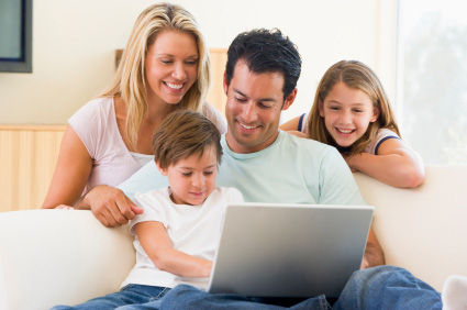 Familj samlad framför bärbar dator